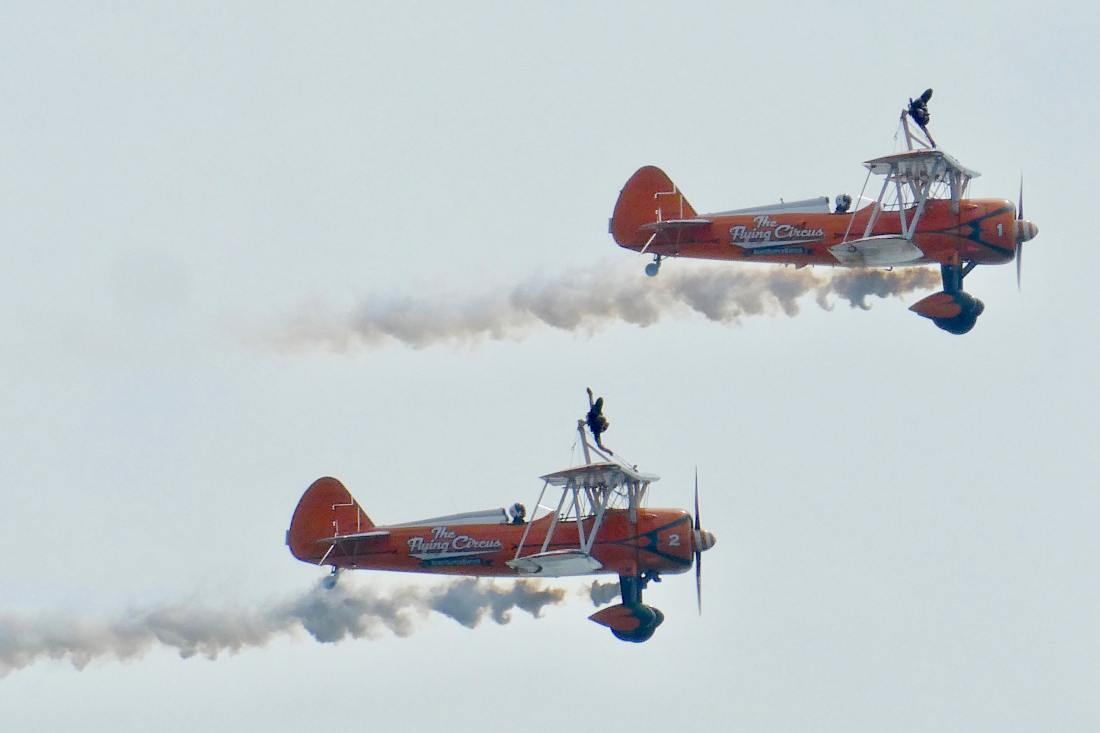 2 planes in tandem with people performing stunt on top of them.